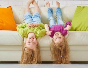 2 cute girls upside down on couch
